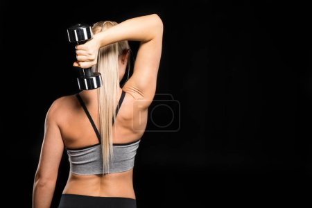 Photo for Back view of young blonde woman exercising with dumbbell  isolated on black - Royalty Free Image