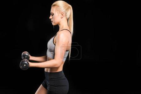 Photo pour Vue latérale de la jeune femme blonde en tenue de sport s'exerçant avec des haltères isolées sur noir - image libre de droit