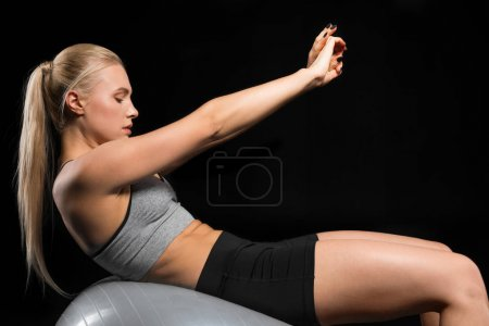Photo for Side view of young sporty woman exercising on fitness ball   isolated on black - Royalty Free Image