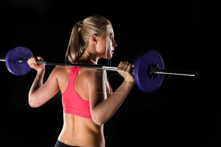 Photo for Back view of woman exercising with barbell isolated on black - Royalty Free Image