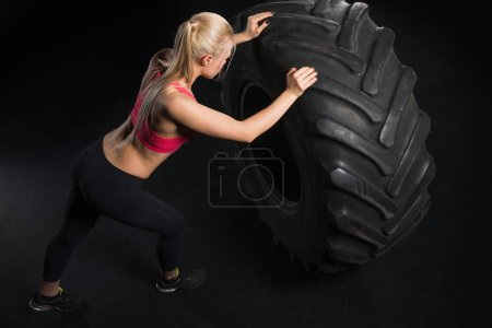 Photo for High angle view of sporty woman exercising with tire isolated on black - Royalty Free Image