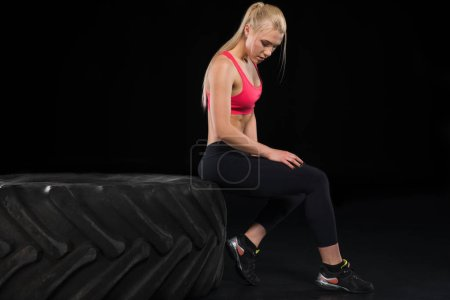 Photo for Side view of woman in sports clothing sitting on tire isolated on black - Royalty Free Image