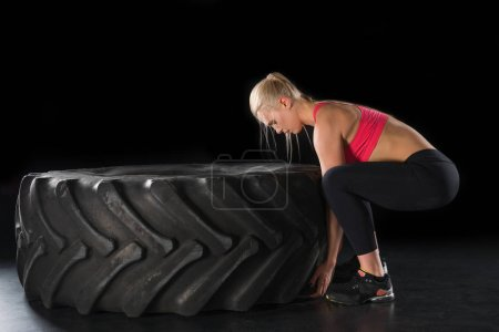 Photo for Side view of sporty woman exercising with tire  isolated on black - Royalty Free Image