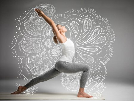 Photo pour Woman practicing yoga standing in variation of Warrior I posture or Virabhadrasana One pose on grey background with mandala - image libre de droit