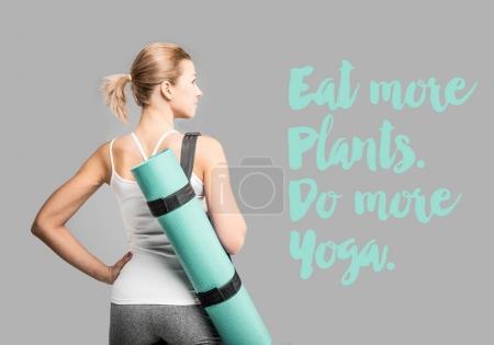 Photo pour Vue arrière de sportive organise des tapis d'yoga sur inscription grise et source d'inspiration - image libre de droit