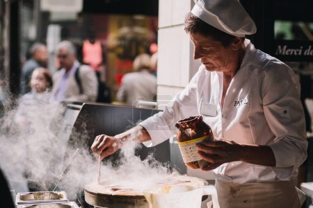 Photo for DEAUVILL, FRANCE - JULY 9,2015: Old Lady preparing food at street, Deauville, Normandy, France - Royalty Free Image