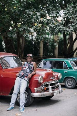 Havana, Cuba - January 6, 2017: man leaning against retro red car
