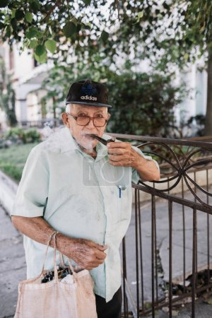 Havana, Cuba - January 5, 2017: local senior man smoking pipe on street