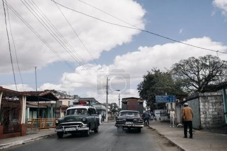 Cienfuegos, Cuba - January 9, 2017: retro cars and locals on street