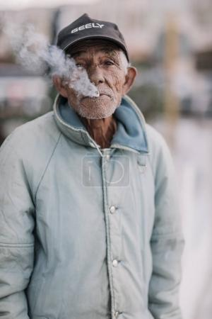 Havana, Cuba - January 8, 2017: local senior man smoking cigarette and looking at camera
