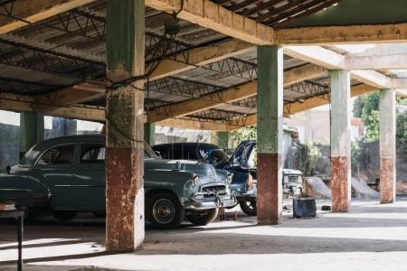 retro cars parked in old parking garage, Trinidad, Cuba