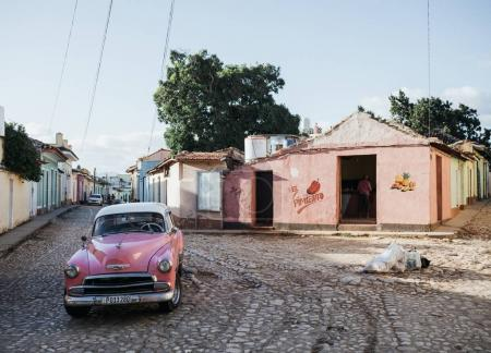 Trinidad, Cuba - January 10, 2017: pink retro car and small colorful houses on street