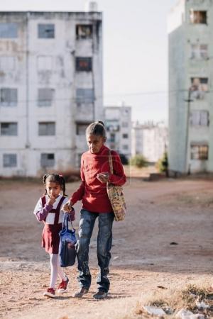 Trinidad, Cuba - January 11, 2017: woman and schoolgirl wearing uniform walking down street