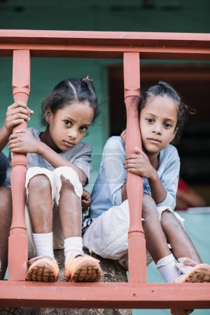 Granma, Cuba - January 20, 2017: girls sitting on wooden fence in front of house
