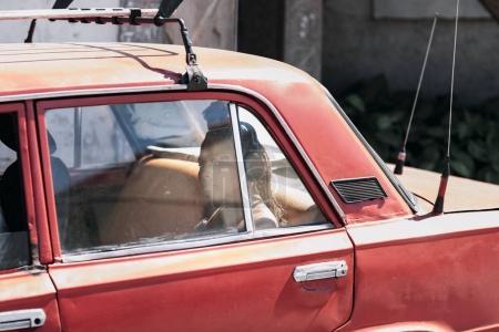 Santiago de Cuba, Cuba - January 20, 2017: local woman sitting in red retro car