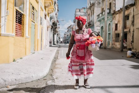 Havana, Cuba - January 22, 2017: colorful dressed woman standing in old town