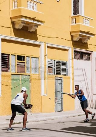 Havana, Cuba - January 22, 2017: two teenagers playing baseball on street