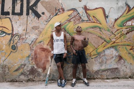 Havana, Cuba - January 22, 2017: two teenagers standing in front of graffiti wall with baseball bat and glove