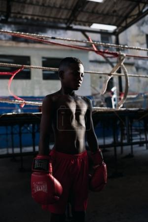 Havana, Cuba - January 22, 2017: boy standing wearing boxing gloves