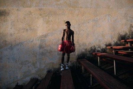 Havana, Cuba - January 22, 2017: boy standing wearing boxing gloves
