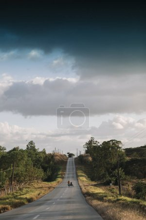 motorbike on roadway with cloudy sky on background, Trinidad, Cuba