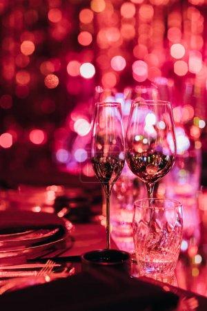 Photo pour Verres à boire et plats à la lumière floue pour la fête - image libre de droit