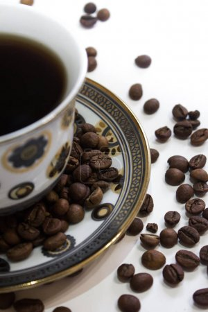 A cup of coffee and coffee beans on a white background