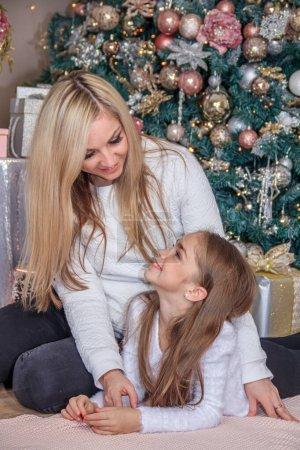 Photo pour Mère et fille posant à côté de l'arbre de Noël - image libre de droit