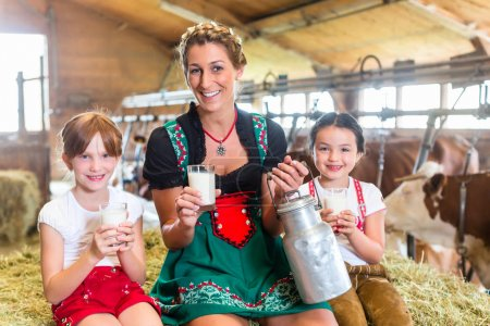 Photo for Bavaria family drinking milk in cowhouse on hay bale drinking fresh milk - Royalty Free Image