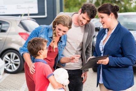 Car dealer advising family on buying auto