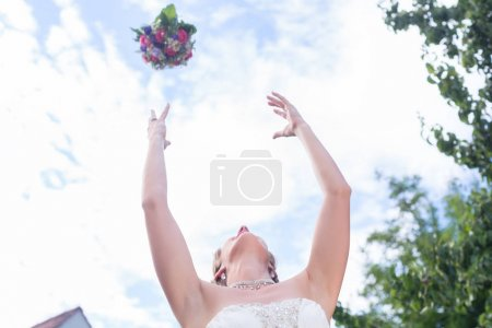 Bride throwing flower bouquet