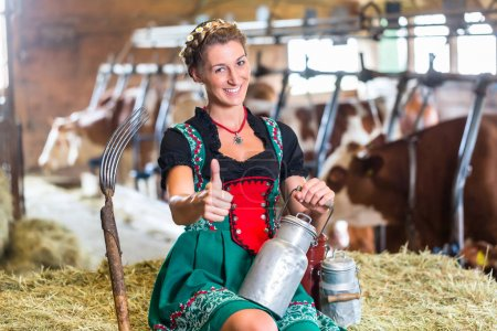 Photo for Bavarian Sexy Countrywoman in cowhouse, milk can and pitchfork in cowhouse - Royalty Free Image