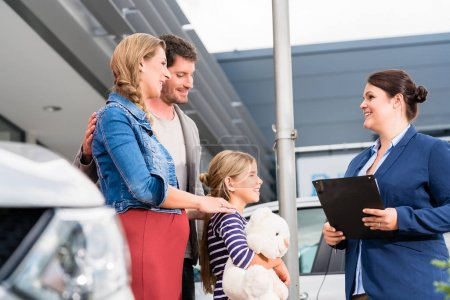 Photo for Car dealer advising family on buying auto showing price list - Royalty Free Image