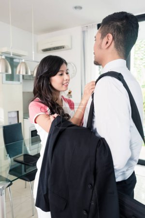 Wife helping her man going to office for work