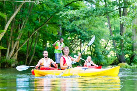 Friends paddling with canoe