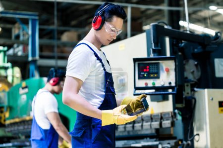 Asian machine operator in production plant