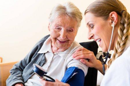 Nurse measuring blood pressure at senior patient