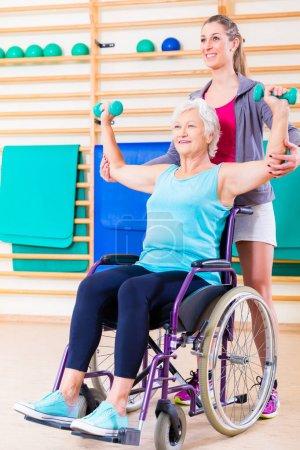 Photo pour Senior femme en fauteuil roulant, faire de la physiothérapie avec son entraîneur - image libre de droit