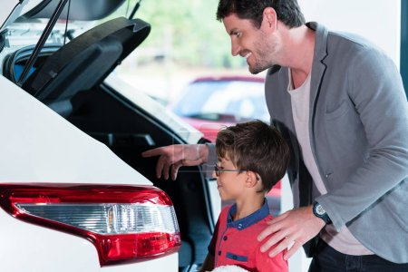 Father and son checking trunk of new car