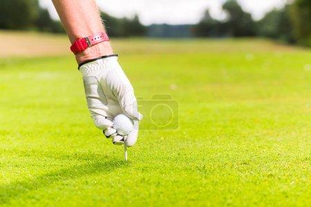 Man putting golf ball on tee