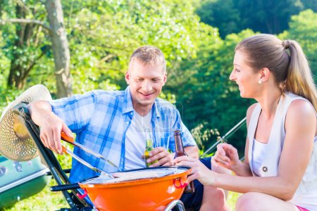 Man and woman having barbeque grilling fish