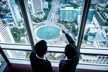 Two Asian businesspeople looking down to city streets