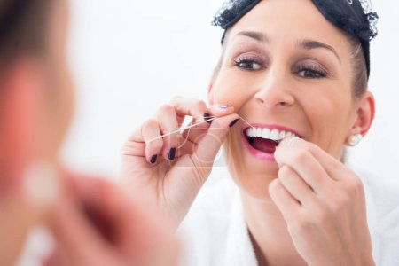 Woman cleaning teeth with dental floss