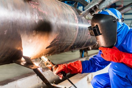 Photo pour Soudeur dans l'usine de soudure des tuyaux en métal - image libre de droit