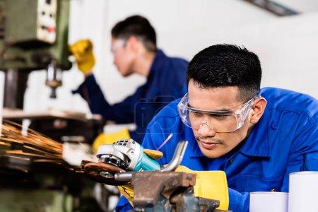 Metal workers in industrial workshop grinding