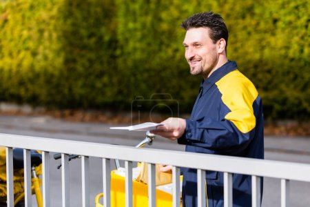Photo for Postman delivering packet wrapped as present - Royalty Free Image