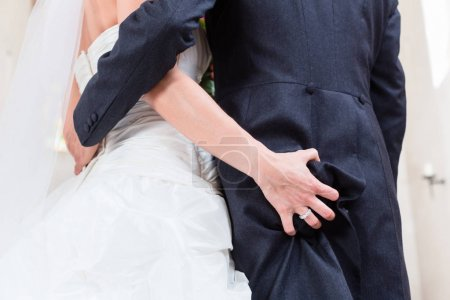 Photo pour Bride grabbing ass of groom at wedding in church - image libre de droit