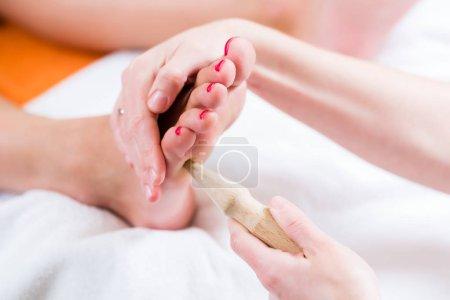 Women at reflexology having foot massaged
