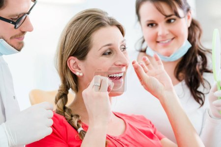 Photo pour Femme chez le dentiste en utilisant la soie dentaire, le médecin expliquant l'utilisation appropriée - image libre de droit