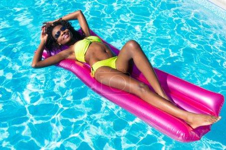 Photo pour Femme africaine nageant sur matelas gonflable dans la piscine en été - image libre de droit